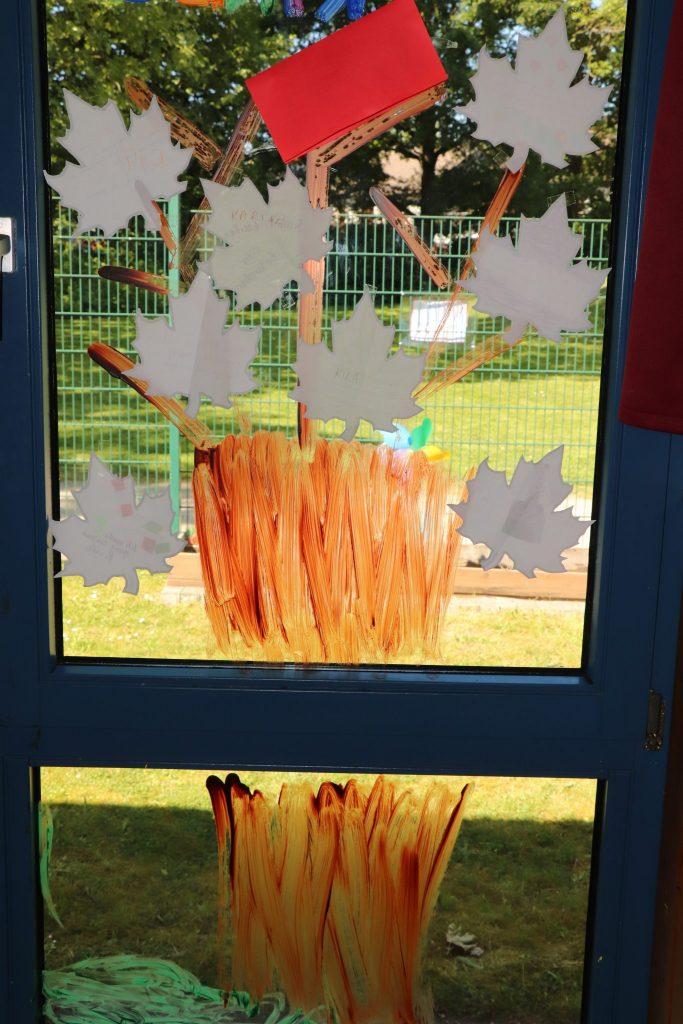 Ein Baum ist auf ein Fenster gemalt. An den Zweigen hängen Blätter aus Papier. Darauf stehen die Wünsche der Kinder und Eltern.